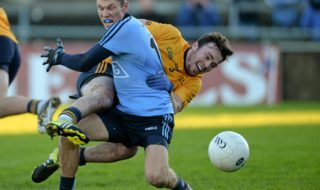 DCU's Conor Moynagh battles with Darren Daly for the ball. Credit: Sportsfile