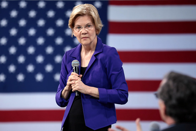 Elizabeth Warren listening to someone in the audience, with the American flag behind her