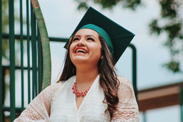 Woman wearing a graduation hat, smiling